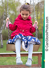 Cute little girl playing on playground in spring. Child in red jacket and blue dress with flowers on a swing on green spring park background