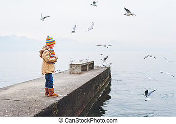 Cute little girl playing outdoors next to lake Geneva on a cold weather, feeding birds in winter time