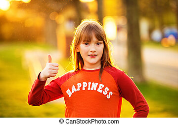 Cute little girl playing outdoors on a nice summer evening, wearing red t-shirt with sign Happiness, big thumb up, warm sunset backlight