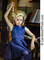 Cute little girl playing piano, dressing in retro Mozart periwig