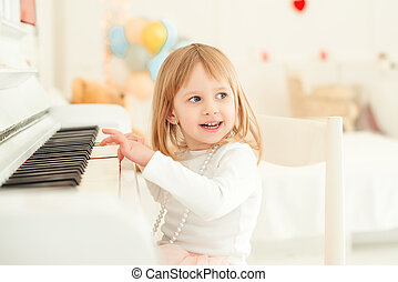 Cute little girl playing piano in light room.