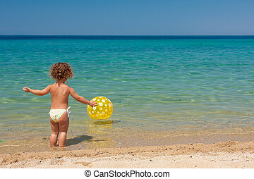 b06d742574 Little girl with a ball at the beach. Small girl standing with a ...