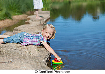 Cute little girl playing with a boat