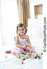 Cute little girl playing with alphabetics blocks