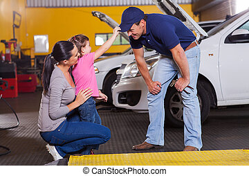 cute little girl playing with auto mechanic in garage