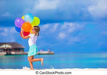 Cute little girl playing with balloons at the beach