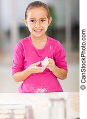 cute little girl playing with bread dough