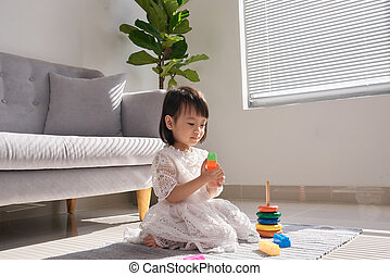 Cute little girl playing with building blocks on floor at home