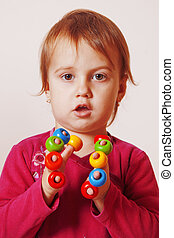 cute little girl playing with colored toys