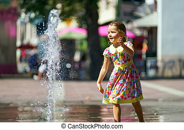 Cute little girl playing with fountain splash