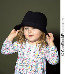 Cute little girl playing with hat