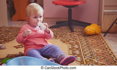 Cute little girl playing with her toys and smiling, sitting...