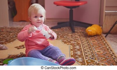 Cute little girl playing with her toys, sitting on the floor