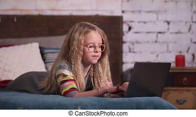 Cute little girl playing with laptop on the bed