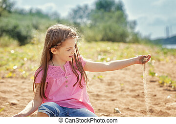 Cute little girl playing with sand in park
