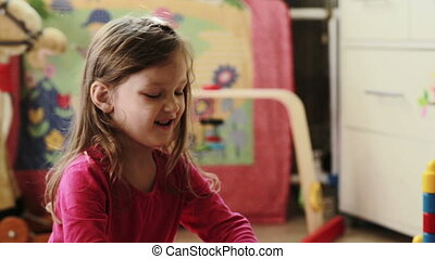 Cute little girl playing with toy blocks at home