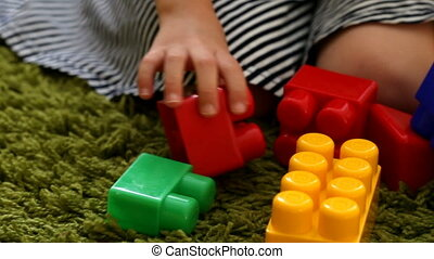 Cute little girl playing with toy blocks, closeup