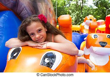 Cute little girl plays in bouncing castle - Cute little...