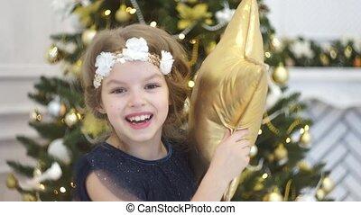 Cute little girl plays near the Christmas tree.
