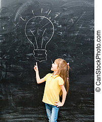 cute little girl pointing on a drawn lamp