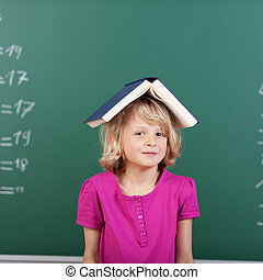 Cute little girl posing with a book on her head