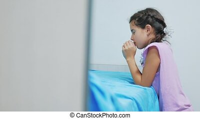 Cute little girl praying at home. little girl prays in the evening before bedtime bed. lifestyle little girl and religion concept Faith in God