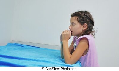 Cute little girl praying at home. little girl prays in the evening before bedtime bed. little girl and religion concept Faith in God lifestyle