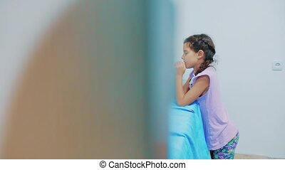 Cute little girl praying at home. little girl prays in the...
