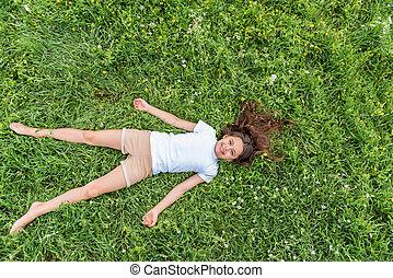 Cute little girl relaxing on grass in summer