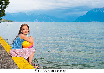 Cute little girl resting by the lake at sunset
