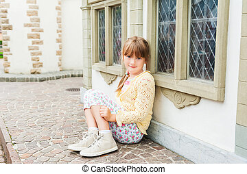 Cute little girl resting outdoors