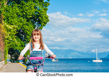 Cute little girl riding on a bicycle by the lake