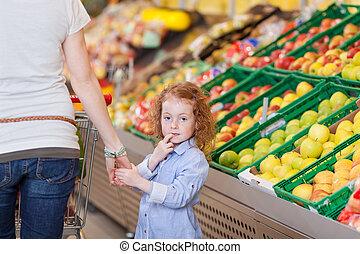 Cute little girl roaming in the supermarket