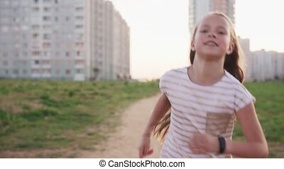 Cute little girl running against urban wasteland, slow...