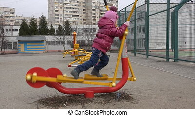 Cute Little Girl Running on Elliptical Trainer in the Open Air Gym