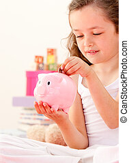 Cute little girl saving money in a piggy-bank sitting on her bed at home