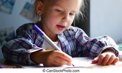 Cute Little Girl Sits at Her Table and Draws