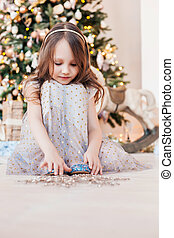 Cute little girl sitting against Christmas tree and playing with xmas decoration.