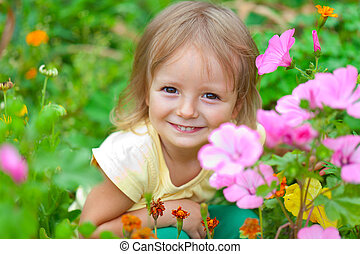 Cute little girl sitting among the flowers. Sunny summer day