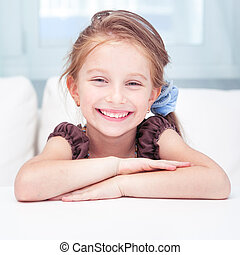 cute little girl sitting at a desk in light room at home