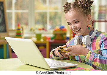 Cute little girl sitting at the table and playing