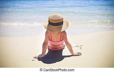 Cute little girl sitting at the tropical beach