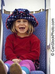 Cute little girl sitting in chair