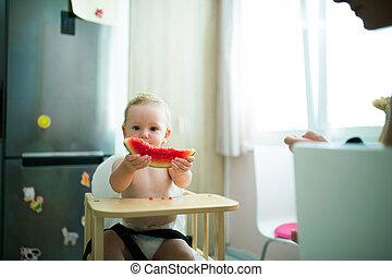 Cute little girl sitting in high chair eating watermelon -...