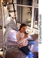 Cute little girl sitting inside childrens tent eating cookies
