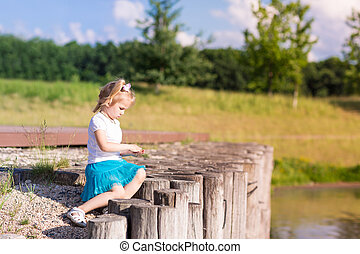 Cute little girl sitting near the lake