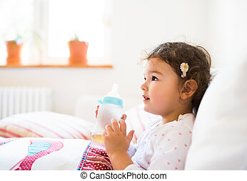 Cute little girl sitting on a couch in living room