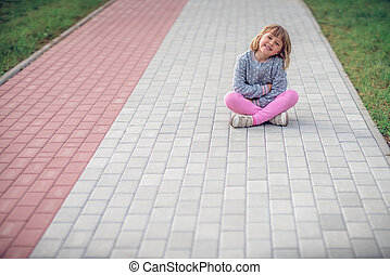 Cute little girl sitting on a pavement