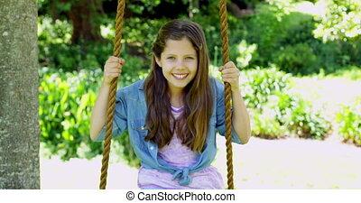 Cute little girl sitting on a swing