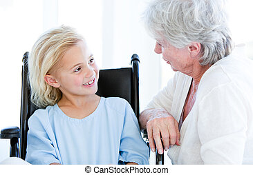 Cute little girl sitting on a wheelchair talking with her grandmother in a hospital